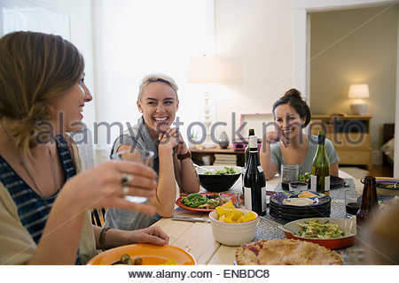 Friends laughing and enjoying dinner party - Stock Photo