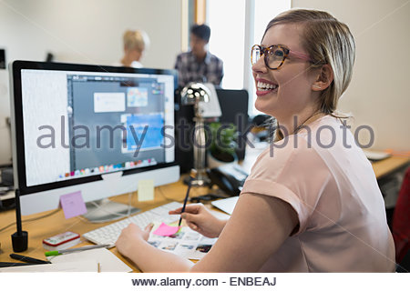 Smiling graphic designer working at computer in office - Stock Photo