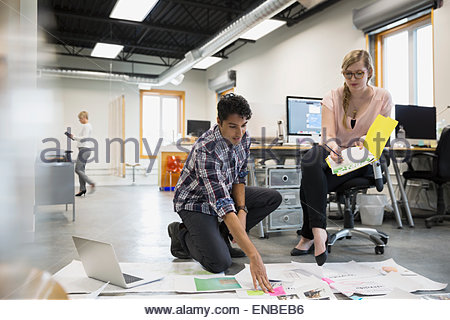 Graphic designers meeting reviewing proofs on office floor - Stock Photo