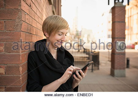 Smiling woman texting cell phone on urban street - Stock Photo