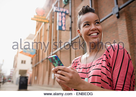 Smiling woman with mohawk texting on urban street - Stock Photo