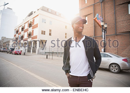 Smiling man crossing urban street - Stock Photo
