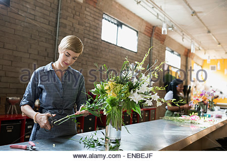 Florist trimming stems arranging bouquet in flower shop - Stock Photo