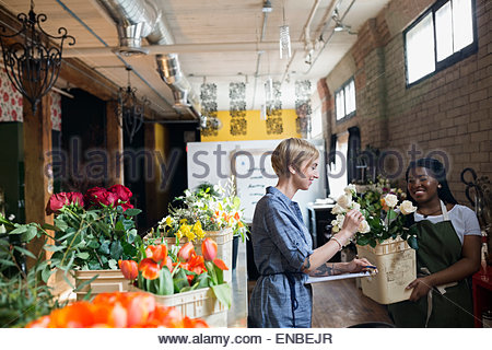 Florists examining fresh roses in flower shop - Stock Photo