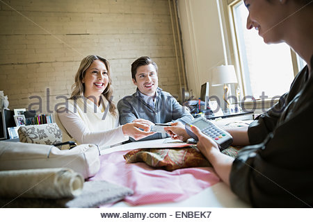 Couple paying interior designer with credit card - Stock Photo