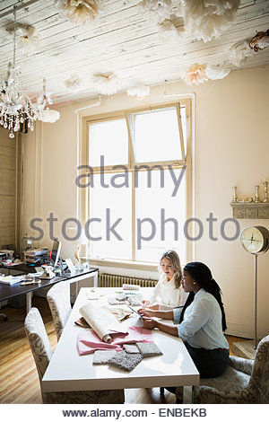 Interior designers looking at swatches in office - Stock Photo
