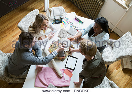 Interior designers showing couple swatches in office - Stock Photo