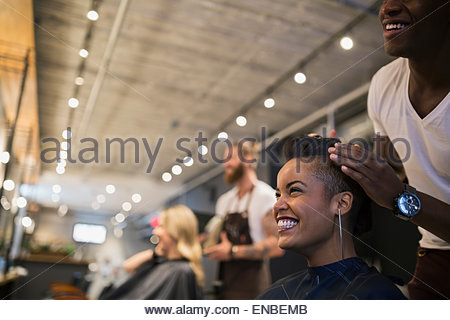 Smiling woman getting hair styled in hair salon - Stock Photo