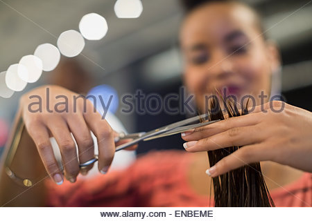 Close up hairstylist cutting hair in hair salon - Stock Photo