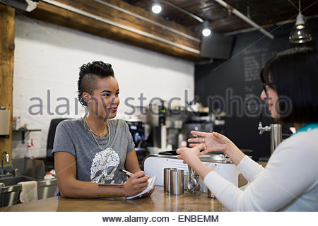 Woman taking order at coffee shop counter - Stock Photo