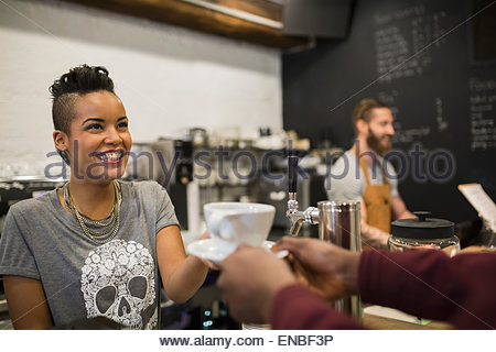 Smiling barista serving coffee to customer in cafe - Stock Photo