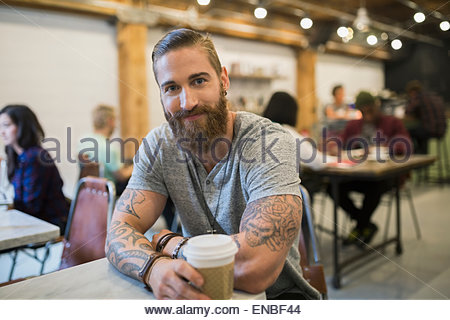 Portrait confident bearded man with tattoos drinking coffee - Stock Photo