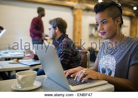 Woman typing on laptop in cafe - Stock Photo