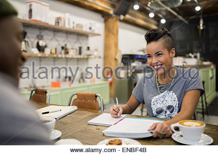 Smiling couple studying in cafe - Stock Photo
