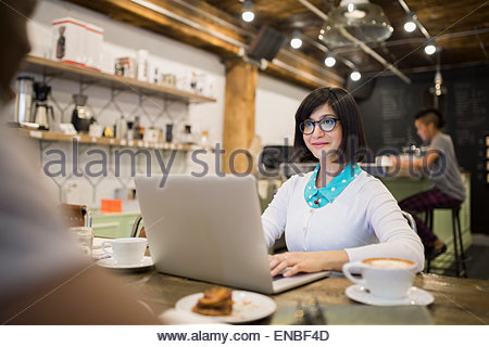 Woman working at laptop in cafe - Stock Photo