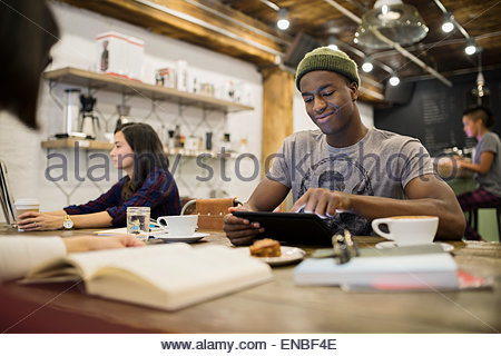 Man using digital tablet in cafe - Stock Photo