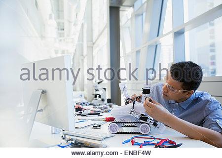 Focused engineer assembling robotic car - Stock Photo