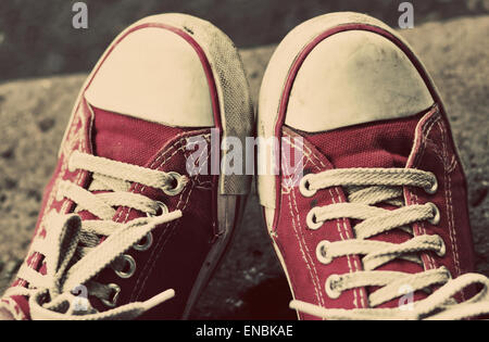 Feet in dirty red sneakers and jeans outdoors. Making first step. Vintage toning. - Stock Photo