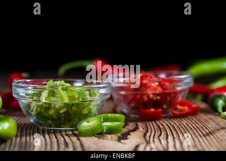 Mixed cutted Chilis (red and green) on vintage wooden background - Stock Photo