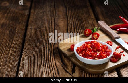 Red Chilis (cutted) on vintage wooden background - Stock Photo