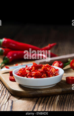 Cutted red Chilis in a bowl (close-up shot) on wooden background - Stock Photo