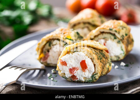 Omelette rolls with curd and herbs on a plate - Stock Photo