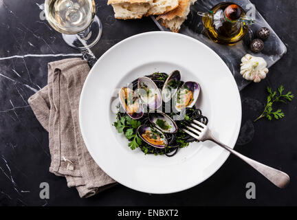 Seafood pasta with clams Spaghetti Vongole on white plate on dark marble background