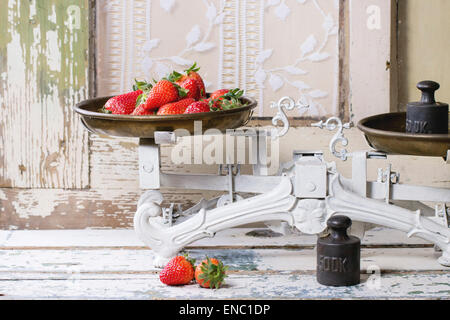 Weights and vintage scales with fresh strawberries over white wooden table - Stock Photo