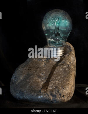 A creative image of hydro energy depicted by a splash of water in a light bulb placed on a rock - Stock Photo