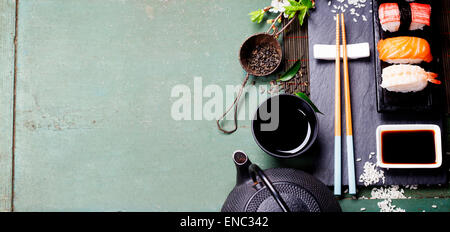 Asian food background (black iron tea set and sushi on rustic table) - Stock Photo