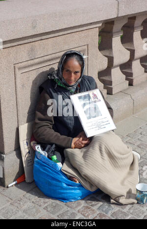 Middle aged Roma woman begs for alms on the Kungsportsbrun bridge, Gothenburg, Sweden - Stock Photo