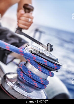 Holder of rope on sailboat, man pulling handle of spool, macro photo of yacht detail, working on water transport, - Stock Photo