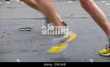 Detail of legs and yellow shoes of 2015 London Marathon competitors running along Upper Thames Street London UK - Stock Photo