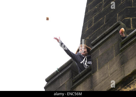 Rotherham, UK. 2nd May 2015. A church member throws a piece of bread from the church tower at Wath All Saints Parish Church near Rotherham, South Yorkshire. One hundred bread bun are thrown to the waiting crowds below as part of the annual Wath Festival. Picture: Scott Bairstow/ Alamy