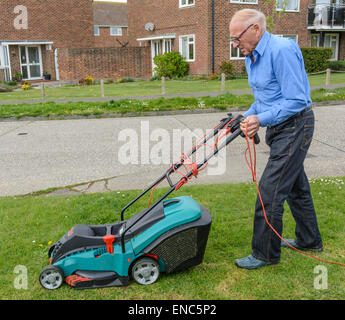 Old man mowing the grass verge by the roadside in West Sussex, England, UK. - Stock Photo