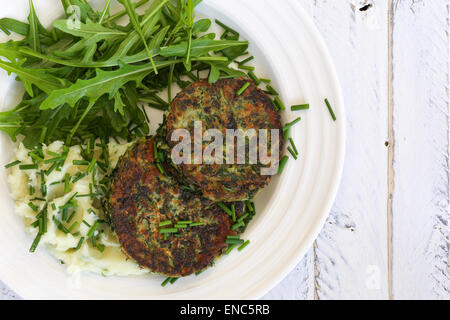 Swiss chard veggie fritters with mash potatoes and rocket leaves on white plate and white rough background, copy - Stock Photo