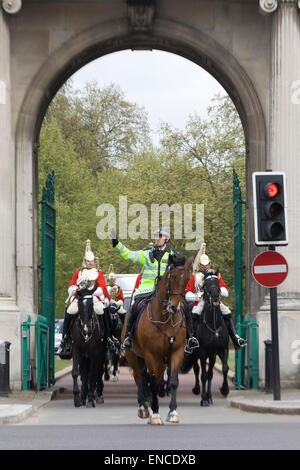 Mounted police officer stopping traffic for the Horse Guards to cross a road in London - Stock Photo