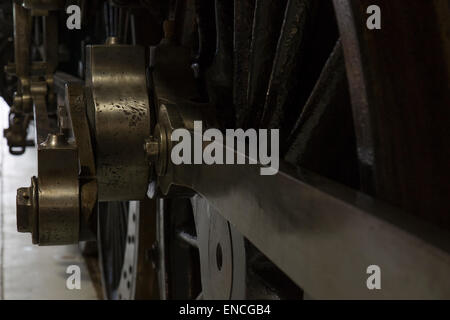 Brass steam train wheel. Brass train mechanics detail. Pistons, rods and connecting arm detail. - Stock Photo