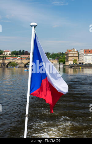 Czech flag flying from the back of a boat on the Vltava River in Prague with the Charles Bridge in the background. - Stock Photo