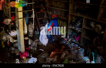 Sankhu, Nepal. 02nd May, 2015. A man gather his belongings from his partially damaged house as he move to temporary - Stock Photo