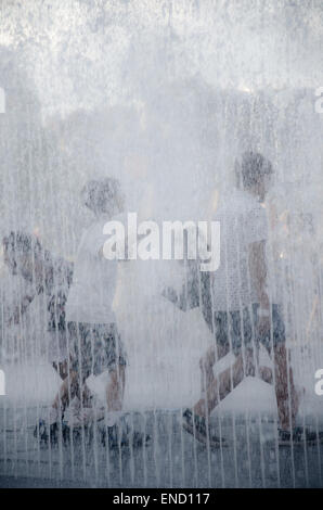 Children playing in a water fountain to cool during a summer heat wave in London - Stock Photo