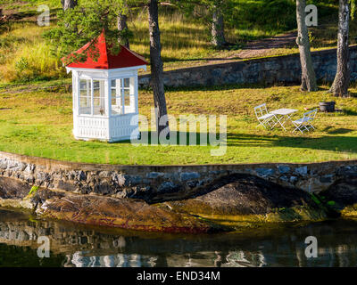 Garden house, table and chairs on a small island in the Stockholm archipelago of Sweden - Stock Photo