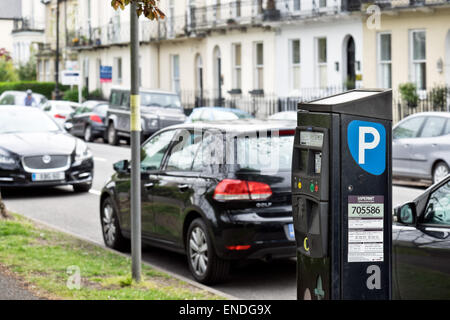 Cars parked by a meter along a parking controlled street in Cheltenham, Gloucestershire, UK - Stock Photo