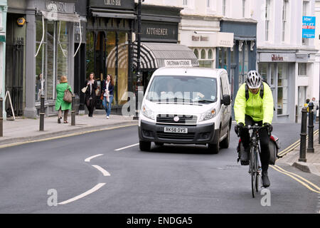 A van overtaking a cyclist wearing safety clothing on a shopping street in Montpellier, Cheltenham, UK - Stock Photo