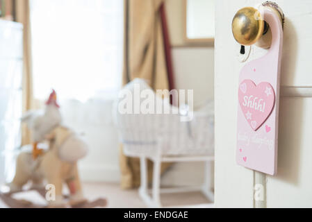 An open door into a babies nursery bedroom,a sign hangs from a brass door knob with the motif 'shhh' written within - Stock Photo