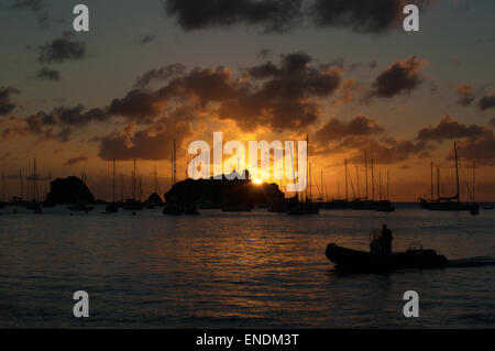 Saint-Barthélemy, French West Indies, French Antilles, Caribbean: a man on a dinghy at sunset in the marina of Gustavia - Stock Photo