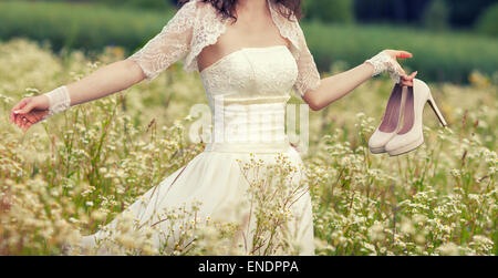 Young bride walking on flower meadow - Stock Photo