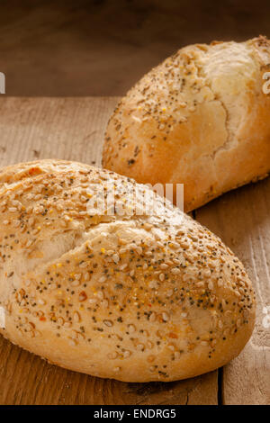Rustic seeded baguettes small freshly baked bread rolls crusted with poppy and sesame seeds - Stock Photo