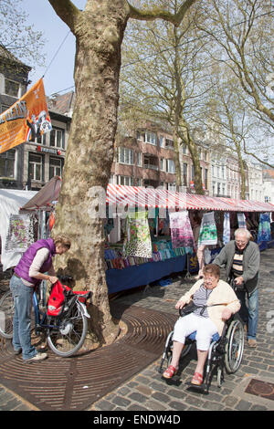 man pushes woman in wheelchair on market in the dutch town of breda - Stock Photo