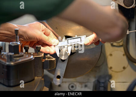 Hands of a male mechanical engineer while measuring a metallic piece with an accurate caliper, at workbench - Stock Photo